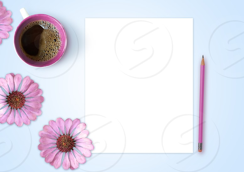Empty sheet of paper pencil cup of coffee and pink flowers on light blue background photo