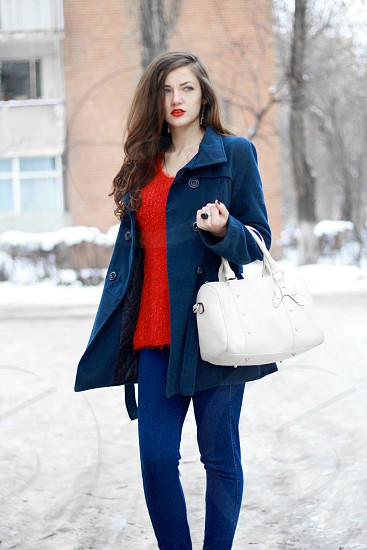 woman wearing blue topcoat red inner top and blue denim pants while holding a white leather handbag at the snowfield photo