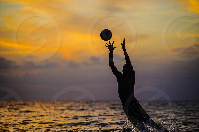Catching a ball. Silhouette of a man jumping out of sea water. photo