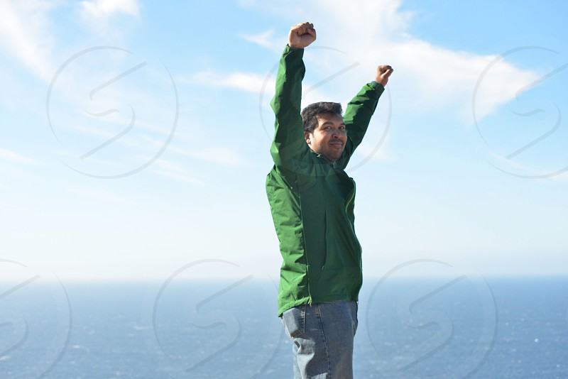 man in green jacket raising both hands with view of ocean at distance photo