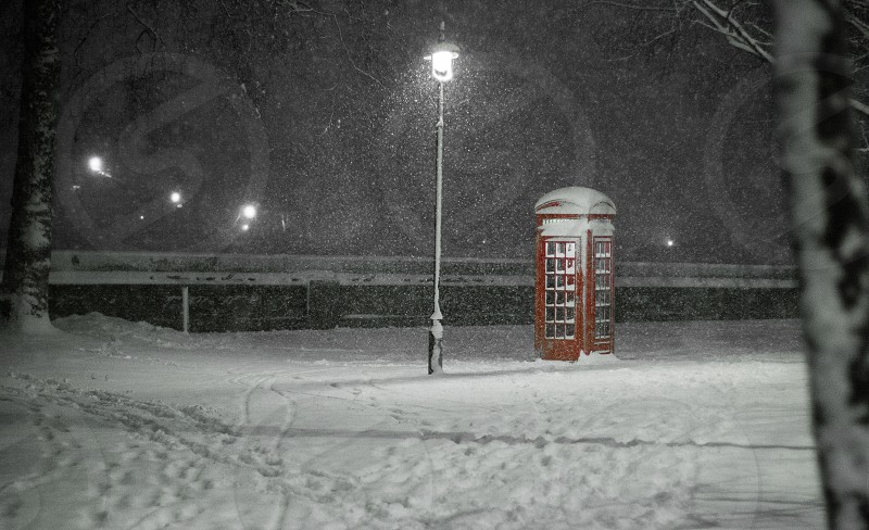 Snow falls on red telephone box streetlight & footprints in the snow Embankment City of Westminster London UK photo