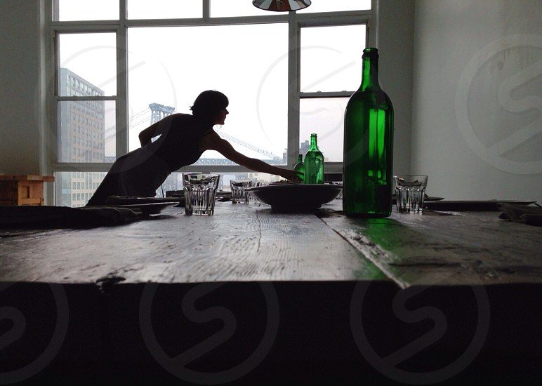 woman trying to reach green beverage bottle on brown wooden table photo
