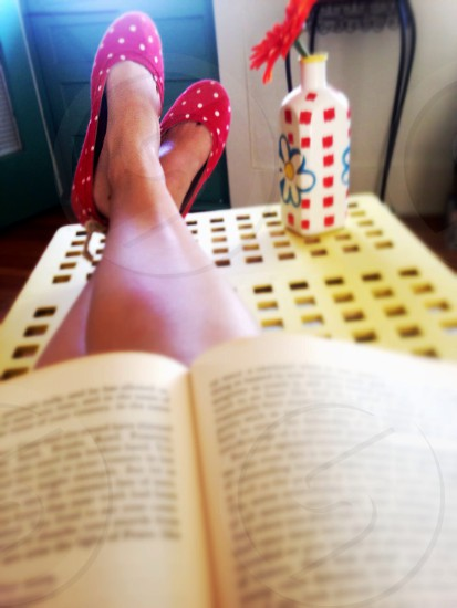 person lying with book on lap photo
