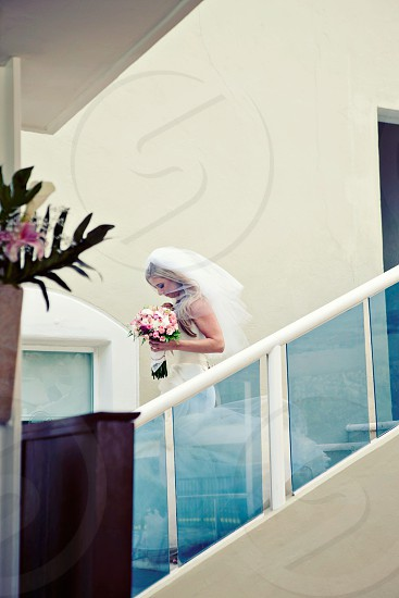 woman in white wedding dress holding a pink bouquet walking down the stairs photo