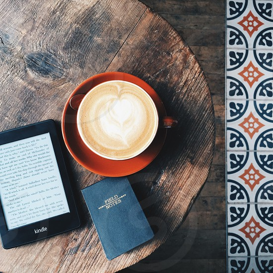 field notes beside black kindle e-book reader and brown ceramic cup photo