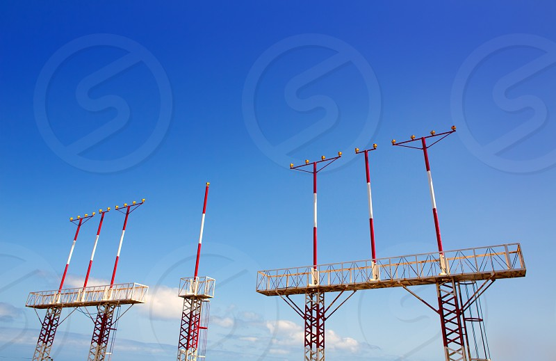 Landing lights towers in white and red over blue sky in Canary Islands photo