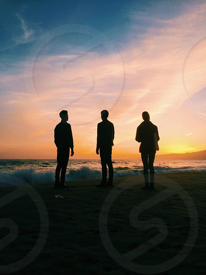 three man standing on brown sand seashore photo