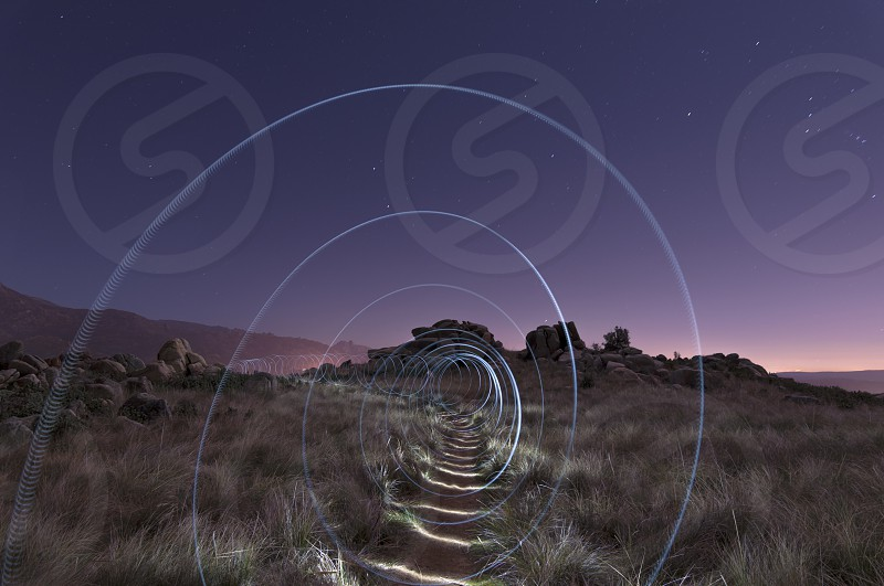 Painting a bright spiral on the hill at night photo