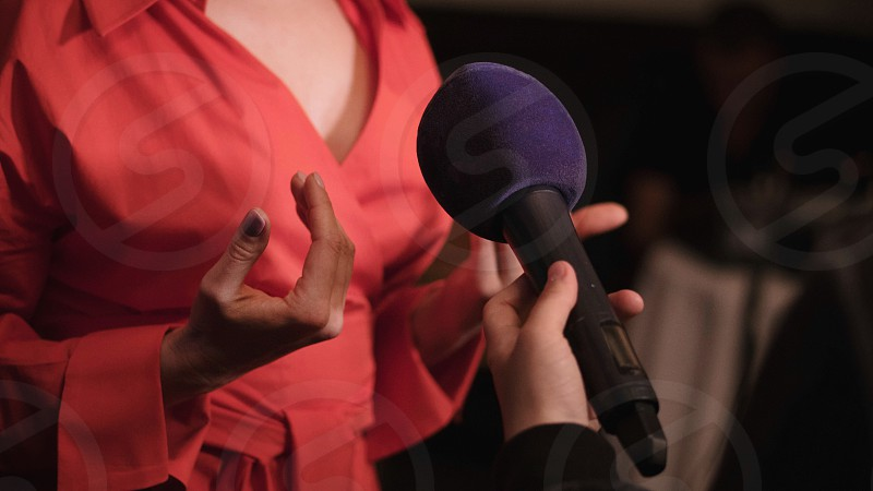 A woman in a red dress speaks into the microphone and gives an interview to the TV channel photo