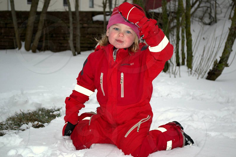 girl in red and white overalls sitting on white snow photo