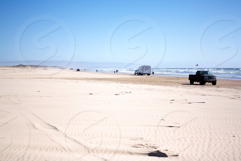 two vehicles in beach under clear blue sky photo