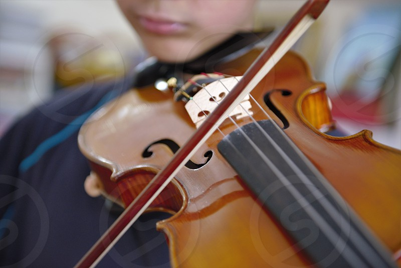 Young boy playing a violin in his home in Hong Kong.   photo