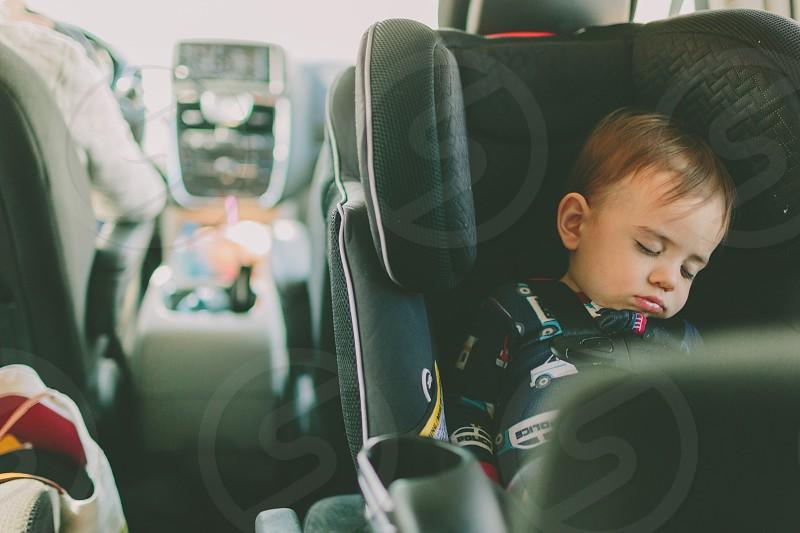 A baby boy asleep in his rear facing car seat. photo