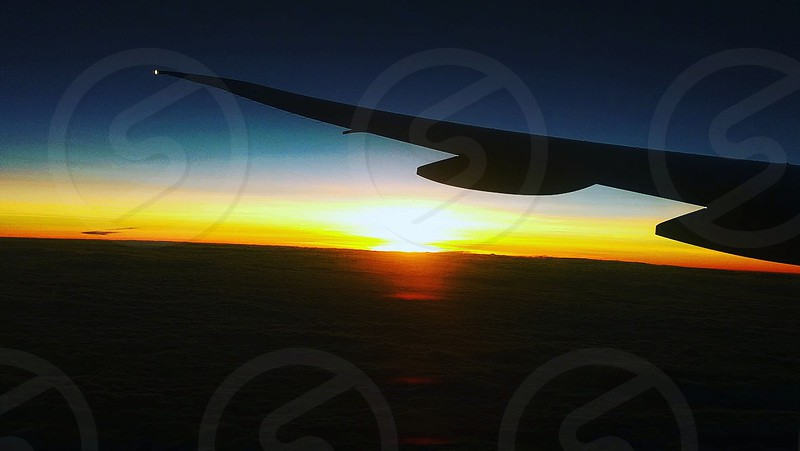 view of sunset from the window by aeroplane wing photo