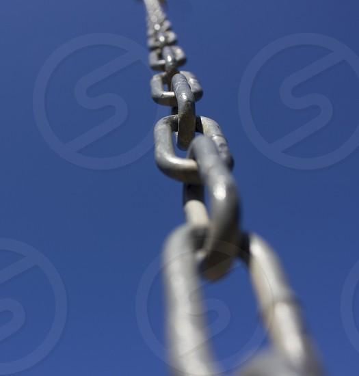 chain link links steel sky blue blue sky macro distortion single object close up photo