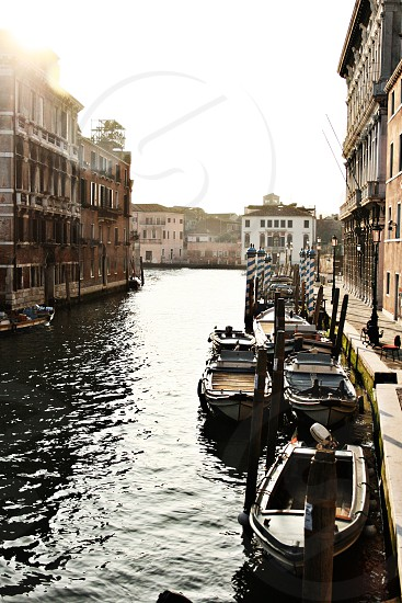 Venice Italy canal with boats and a beautiful sun flare. Water canal gondola Italian boats photo