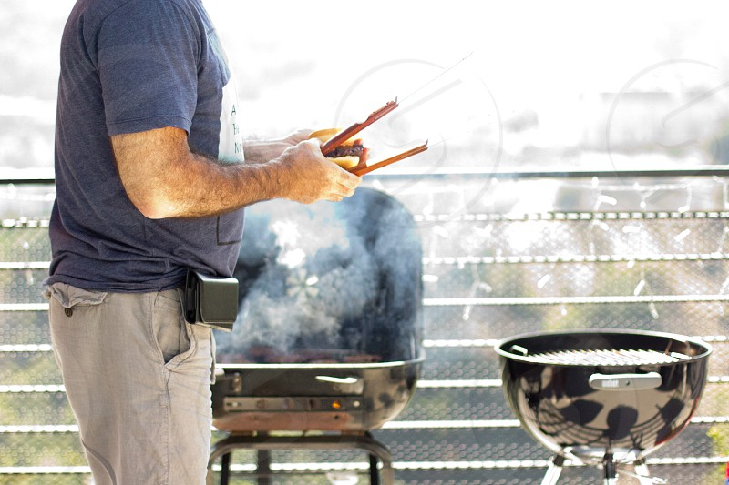 person near barbecue grill and railings making barbecue photo