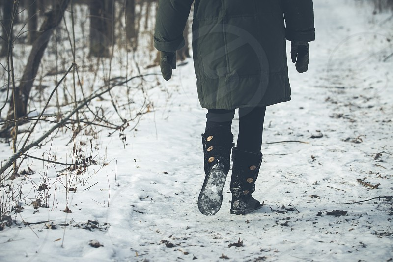 A woman wearing a heavy down coat walks on a path through the woods photo