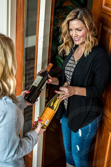 Wine being delivered/gifted to an adult woman at home by another adult woman. photo