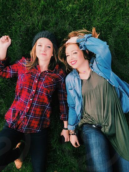 2 women lying on green grass side by side photo