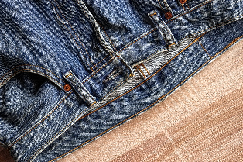 close up front blue jeans texture and details on wooden background photo