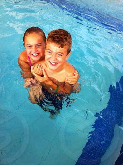 Siblings having pool fun photo