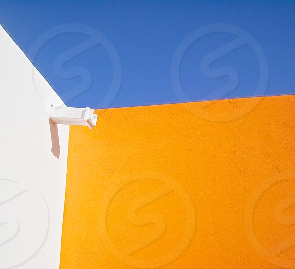 blue sky over white and orange walls with white rain gutter spout photo