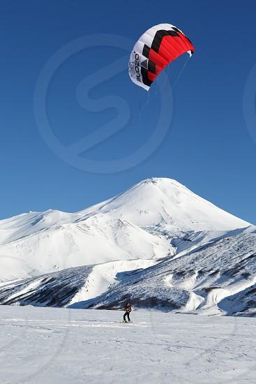 KAMCHATKA AVACHA VOLCANO RUSSIA - NOVEMBER 22 2014: Kiteboarding or Snowkiting - sportsman glides on skis on snow on a background of active Avacha Volcano (Avachinsky Volcano) on sunny day. photo