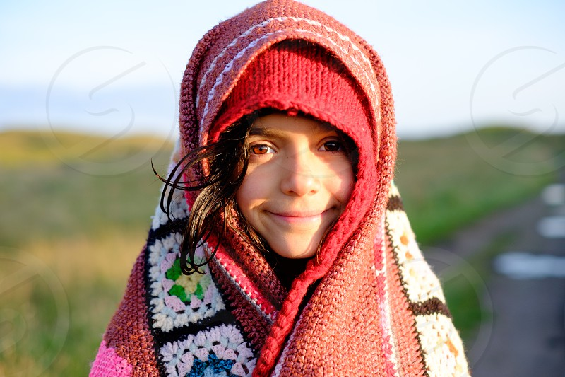 Young mountain girl with a a colourful red crochet blanket wrapped around her head and green fields behind her with evening sunlight behind her. photo