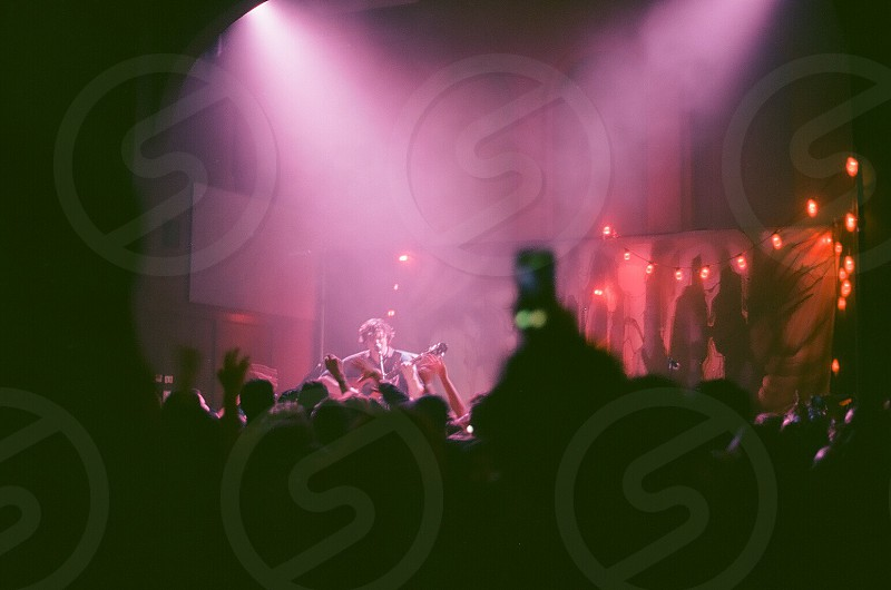 group of people standing in front of concert stage listening to a guy playing guitar photo