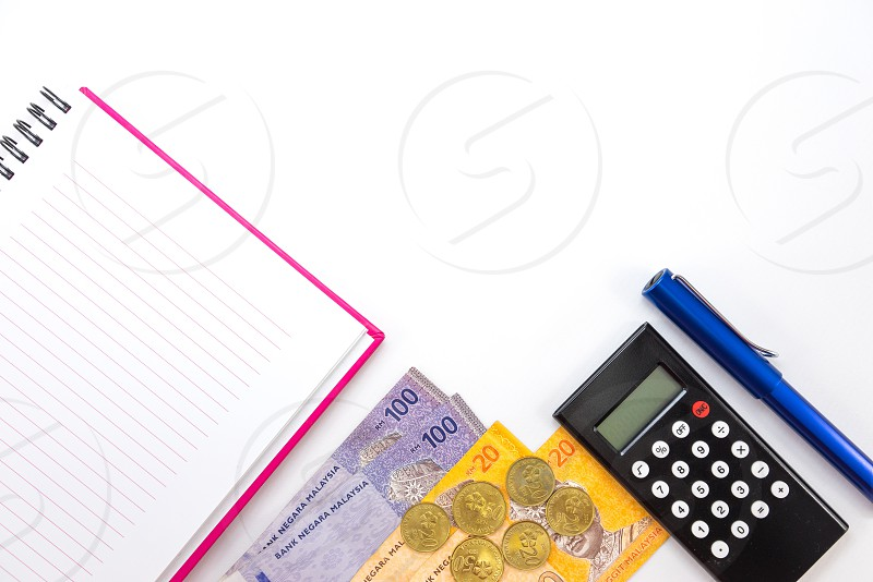 black remote controller beside blue pen and copper coins on top of banknotes and beside spring lined paper notebook photo
