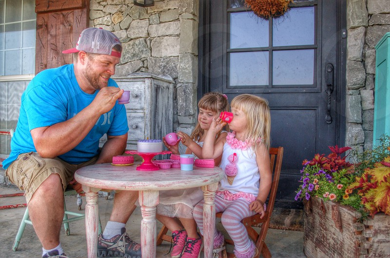 My hubby and little girls having a tea party photo