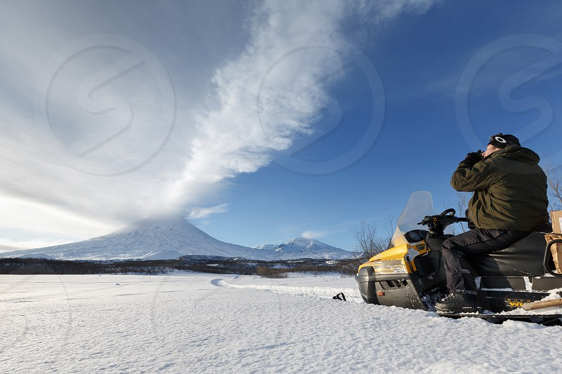 KAMCHATKA PENINSULA RUSSIAN FAR EAST - JAN 4 2016: Tourists and travelers sitting on a snowmobile photographs eruption active Klyuchevskoy Volcano (Klyuchevskaya Sopka) ejected from crater of giant plume of steam gas and ash. photo