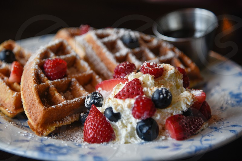 waffle with blueberry and strawberry and white cream on white and blue ceramic floral round plate photo