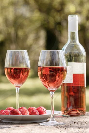 Two glasses of rosé wine next to a bottle of rosé wine of course with strawberries on a plate laid on a table outdoor. Trees can be seen out-of-focus in the background photo