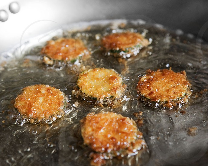 Parmesan zucchini crisps cooking in a skillet. photo