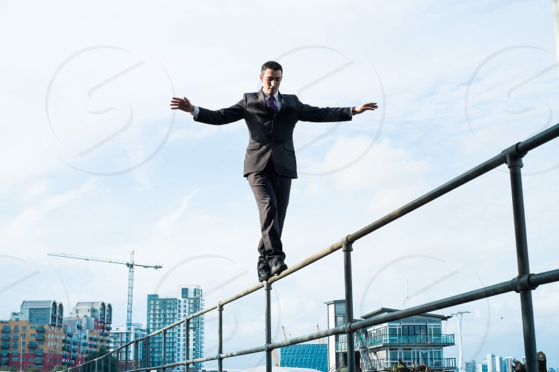Man in suite walking and balancing on a railing photo