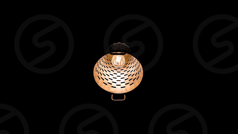 Lit yellow ceiling lamp light surrounded by pitch black darkness photo
