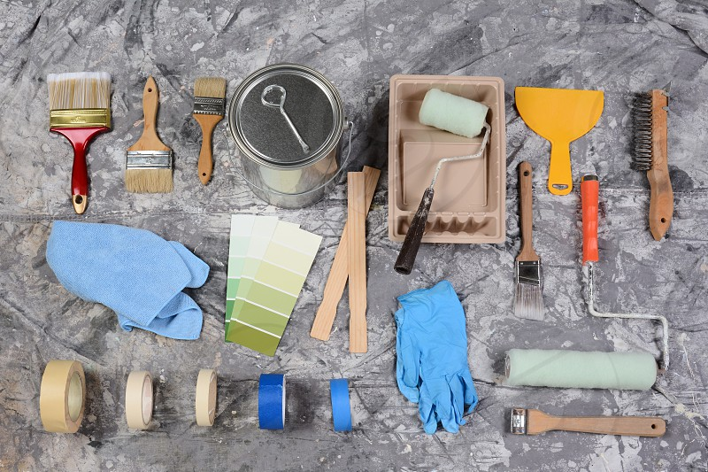 High angle shot of the tools needed to paint spread out on a drop cloth. Items include paint can brushes rollers tray tape color chart rags wood stir sticks scrapers and latex gloves.  photo