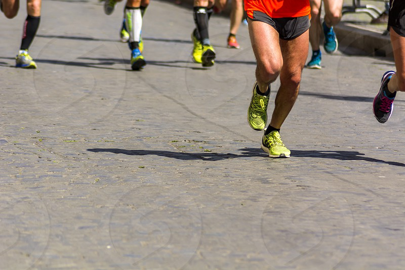 Detail of a group of runners during a city marathon. Legs and sneakers. Muscles under stress. Sport concept photo