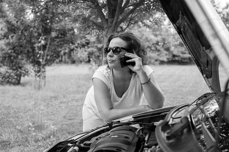 beautiful woman calling help with damaged car broken stop call help mobile cellphone transportation glasses road trip photo