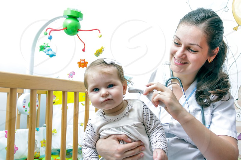 Young nurse consulting baby girl in her room photo