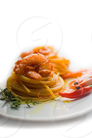italian spaghetti pasta and fresh spicy shrimps sauce over white photo