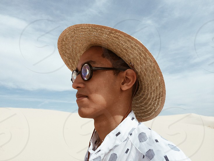 man in grey and black printed button up shirt with eyeglasses and brown woven hat photo