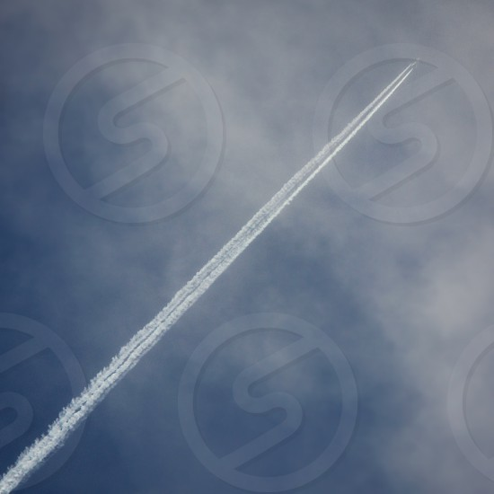 Contrail into the clouds. photo