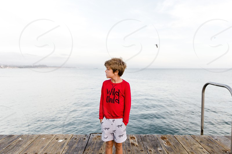 boy with red shirt next to water area photo
