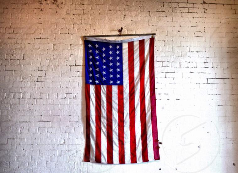 american flag against white brick wall photo