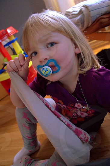girl sipping pacifier photo