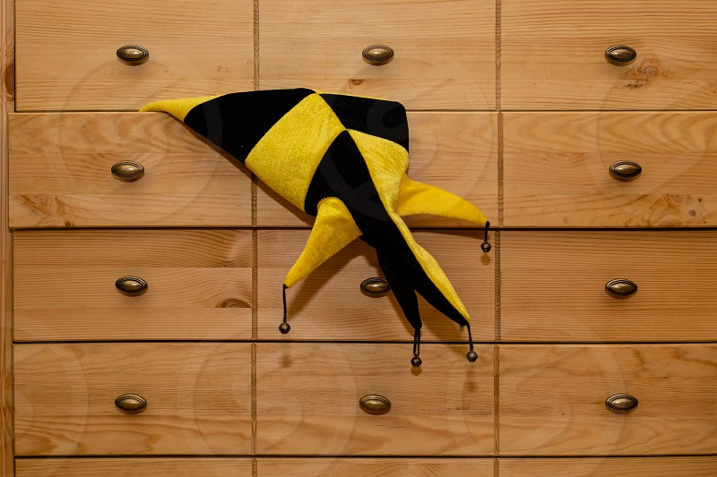 A carnival hat is visible from the chest of drawers. photo