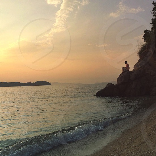 man in black fitted cap sitting on rock facing sea photo
